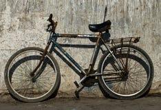 Altes rostiges Fahrrad nahe der Wand Lizenzfreie Stockfotos