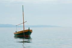 Altes rostiges Fischerboot steht auf dem Wasser, blauer Himmel leer Stockfotos