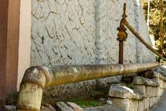 Altes rostiges Gasrohr wird entlang der Straße gepflastert Nahe einem alten Stein Stockfoto