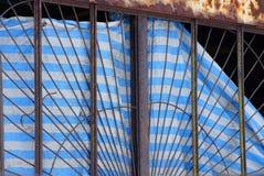 Altes rostiges Gitterfenster mit einem gestreiften Vorhang des heftigen Gewebes stockfotos