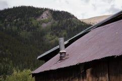 Altes rostiges Metalldach mit Kamin-Entlüftung Stockfotos