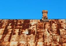 Altes rostiges Metalldach mit Ziegelsteinkamin gegen blauen Himmel Stockfotografie
