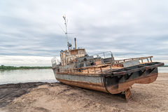 Altes rostiges Schiff auf Sandstrand gegen Flusspanorama an der Dämmerung Stockbild