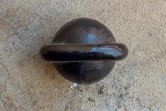 Altes rostiges schwarzes kettlebell auf noncrete Bodenhintergrund Stockbilder