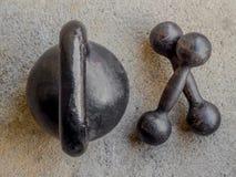 Altes rostiges schwarzes kettlebell und zwei kleine Dummköpfe auf noncrete f Stockbilder