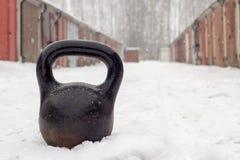 Altes rostiges schweres kettlebell für Wintertraining auf weißem Schnee bedeckte Straße in der Garagengemeinschaft Stockfoto