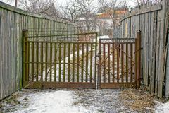 Altes rostiges Tor in der Straße mit einem Bretterzaun Lizenzfreies Stockfoto