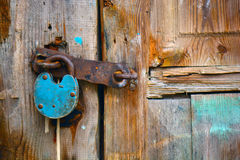 Altes rostiges Vorhängeschloß, das an einer alten Holztür hängt Lizenzfreies Stockbild