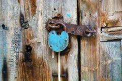 Altes rostiges Vorhängeschloß, das an einer alten Holztür hängt Lizenzfreie Stockfotos
