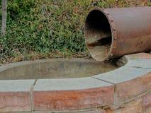 Altes rostiges Weinleseabflussrohr, das in ein Wasserbecken in Gedächtnis-Grove-Park in Salt Lake City Utah entlang dem Wasatch F Stockbild