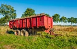 Altes Rot farbiger Ackerwagen auf dem Gebiet Lizenzfreies Stockbild