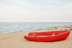 Altes rotes Boot auf dem Strand, Wellen auf dem Wasser und Himmelhintergrund lizenzfreie stockfotografie