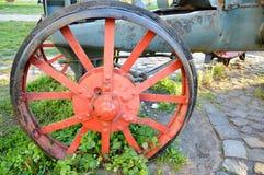 Altes rotes Eisenrad fixierte in das Gras stockbild