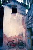 Altes rotes Fahrrad und alte Zementwand mit Sprüngen in einem verlassenen Haus Lizenzfreies Stockbild