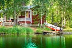 Altes rotes finnisches Sommerhäuschen an einem See Stockfotos