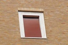 Altes rotes hölzernes Fenster auf Backsteinmauer Stockfotografie