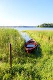 Altes rotes hölzernes Fischerboot mit Wasser am See Stockbild