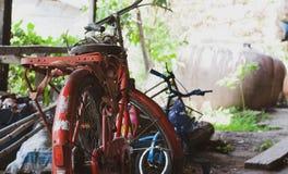 Altes rotes Stahlweinlesefahrrad wird in der sehr alten Garage mit geparkt stockfotografie
