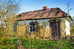 Altes, ruiniertes, Zweig- und Fleckhaus mit zerbrochenen Fensterscheiben Stockfotografie