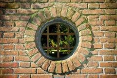 Altes rundes Fenster auf Backsteinmauer Stockfotos