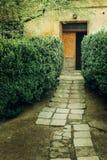 Altes rustikales Gebäude mit Holztüren und geen Garten, italienisches p Stockbild