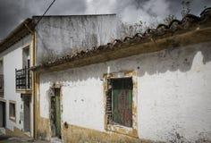 Altes rustikales Haus nahe bei einem modernen Gebäude an einem bewölkten Tag Stockfotos