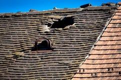 Altes schädigendes mit Ziegeln gedecktes Dach mit einem Loch auf dem Dach und den defekten Fliesen lizenzfreies stockbild