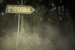 altes Schild mit dem Text psychedelisch nahe dem unheimlichen Wald stockbild
