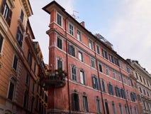 Altes schmales schmutziges rosa Wohngebäude mit rundem Balkon Schöne alte Fenster in Rom (Italien) Stockbild