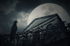 Altes Schmutzgebäude nachts über bewölktem Himmel und dem Mond hinten Lizenzfreie Stockfotografie