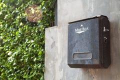 Altes Schwarzes befleckte Metallbriefkasten auf einer grauen Hausmauer Stockfotos