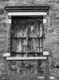 Altes Schwarzes schloss das Fenster Fensterläden, das in eine gebrochene Wand eingestellt wurde Stockbild