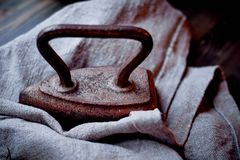 Altes schweres Gusseiseneisen auf einem Stück Leinwand Retro- Foto Stockfoto