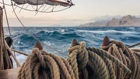 Altes Segelschiff, das auf dem Meer nahe den Felsen läuft Von dem sichernder Stift die Seile stockfoto