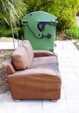 Altes Sofa auf der Straße nahe Abfalleimer Stockbild