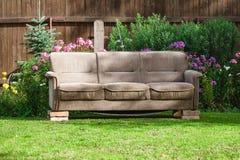 Altes Sofabraun gelegt auf Ziegelsteine in grünen Garten Stockfotografie