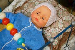 Altes Spielzeug, Weinlesepuppe - Baby in einer blauen Strickjacke in einer Krippe lizenzfreie stockbilder