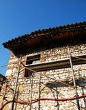 Altes Steinbauernhaus mit Baugerüst Stockfoto