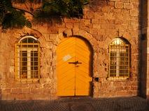 Altes Steingebäude mit gelber Tür und Fenstern Lizenzfreies Stockfoto