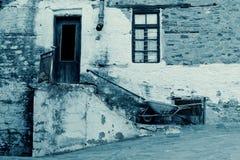 Altes Steinhaus mit Holztür und Fenster, Treppenhaus, Rusty Gutter und Schubkarre I cyan-blau Stockfotos