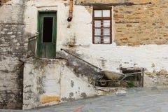 Altes Steinhaus mit Tür und Fenster, Treppenhaus, Rusty Gutter und Schubkarre Lizenzfreies Stockfoto