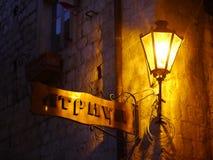 Altes Straßenschild unter Straßenlaterne nachts in Kotor, Montenegro lizenzfreies stockbild