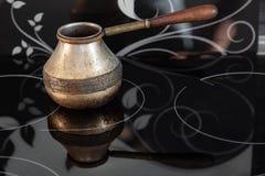 Altes türkisches Retro- Kaffeemaschine Bronzekanaka auf Glasgewindebohrer und Ofen mit dem Holzgriff, getragen auf einem schwarze lizenzfreies stockbild