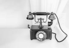 Altes Telefon wird auf einen Holztisch gesetzt Stockfotografie