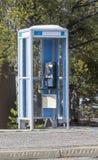 Altes Telefonmünztelefon nahe bei Seite der Tankstelle nahe Bäumen Stockbild