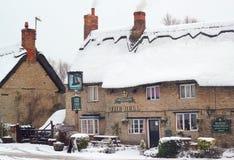 Altes thatched Gasthaus im Schnee. Stockfotografie