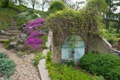 Altes Tor in einem botanischen Garten Wiese voll des gelben Löwenzahns Stockbild