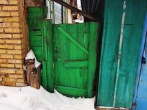 Altes Tor mit einem Zaun am Eingang zu einem Backsteinhaus auf dem Hintergrund des Schnees im Winter stockbilder