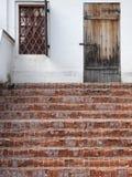 Altes traditionelles Portal mit Ziegelsteintreppe und verschlossener Holztür Lizenzfreie Stockbilder