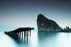 Altes Verfallen und verfallener Pier mit ruhigem See und Felsen stockbild